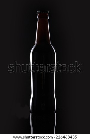 A brown beer bottle reflective bottom isolated black. - stock photo