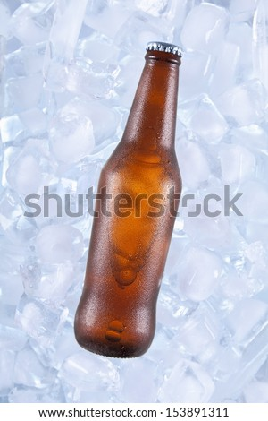 A brown bottle of beer on ice.