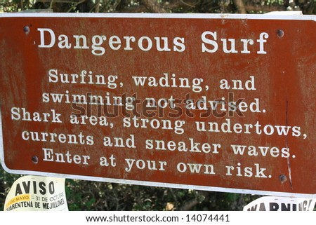 A brown Dangerous Surf sign warning against going in the water - stock photo