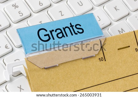 A brown file folder labeled with Grants - stock photo