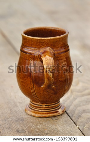 A brown glazed pottery cup from the 17th Century. - stock photo