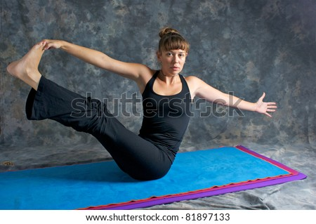 A brown haired caucasian woman is doing yoga exercise, Navasana Pose or Rotated Boat posture  on yoga mat in studio with mottled background. - stock photo