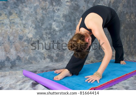 A brown haired caucasian woman is doing yoga exercise, Pyramid Pose or Parsvottonasana posture  on yoga mat in studio with mottled background. - stock photo