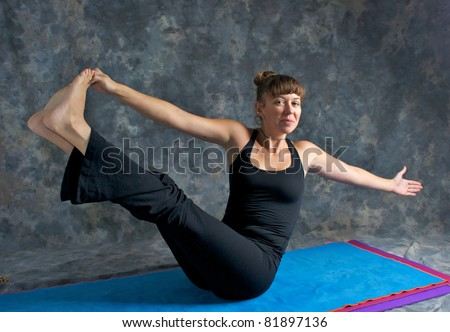 A brown haired caucasian woman is smiling doing yoga exercise, Navasana Pose or Rotated Boat posture  on yoga mat in studio with mottled background. - stock photo