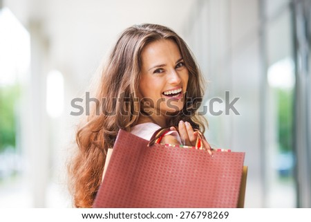 A brown-haired woman holding shopping bags - with a brown, textured bag most prominent - over her right shoulder looks back at the viewer in total happiness.