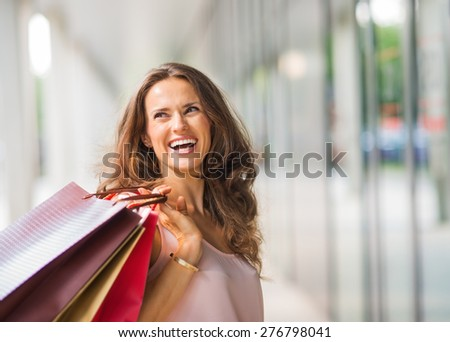 A brown-haired woman holding three shopping bags - brown, gold, and red - over her right shoulder looks back at someone who is making her laugh. A good shopping spree makes any woman happy.  - stock photo