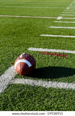 A brown leather American football on a green football field - stock photo