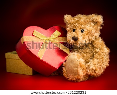 A brown teddy bear sitting and hugging a heart shaped box with a bow ribbon isolated against a red and black background. - stock photo