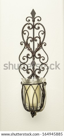 a brown wall candle holder isolated on a tan background