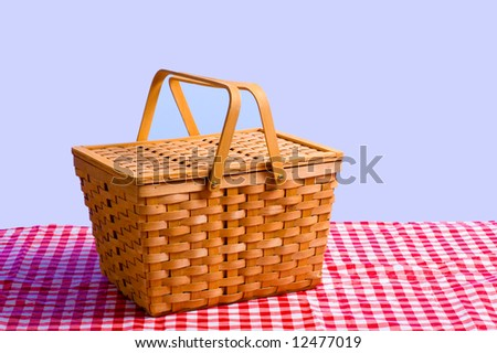 a brown wicker antique picnic basket on a gingham tablecloth in front of a blue sky - stock photo