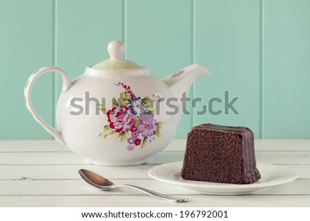 A brownie on a plate. A teapot and a spoon on a white wooden table with a robin egg blue background. Vintage style. - stock photo