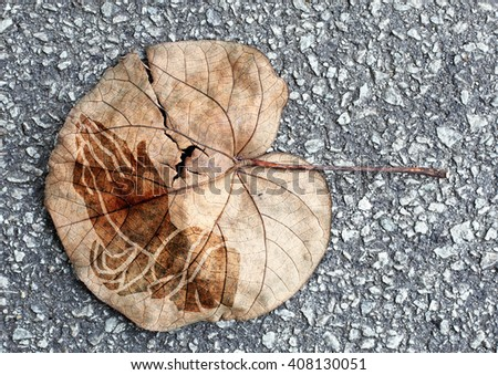 A browning leaf with imprint of a pair of praying hand the concept of praying to save our environment. - stock photo