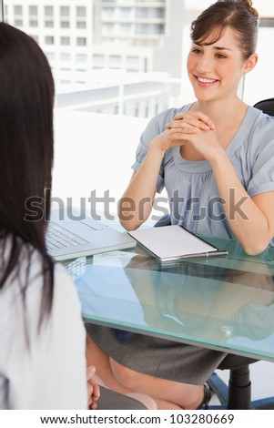 A brunette business woman chats with her other co worker - stock photo