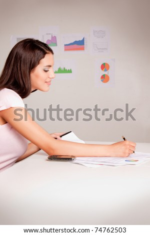 A brunette business woman looking at some numbers and graphs - stock photo