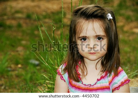 A brunette child looking very serious sitting outdoors