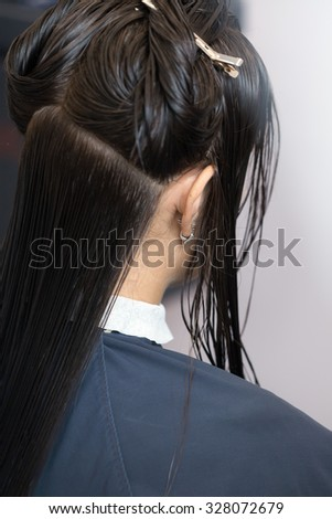 A brunette girl having her haircut. Selective focus - stock photo