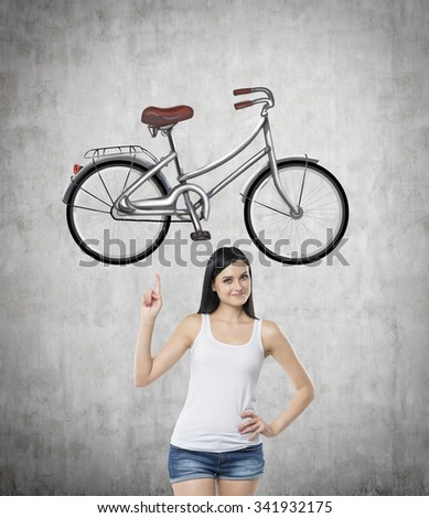 A brunette girl in a white tank top and denim shorts points out the bicycle by her finger. A sketch of bicycle is drawn on the concrete wall. - stock photo