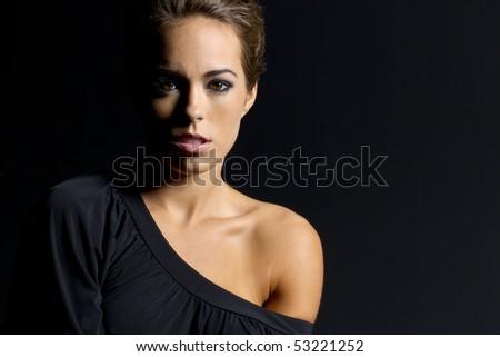 A brunette model posing on black in a studio environment - stock photo