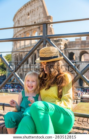 A brunette mother wearing a hat in the summer in Rome is sitting next to her blonde, smiling daughter. They are happy. In the distance, the Colosseum and summer tourists. - stock photo
