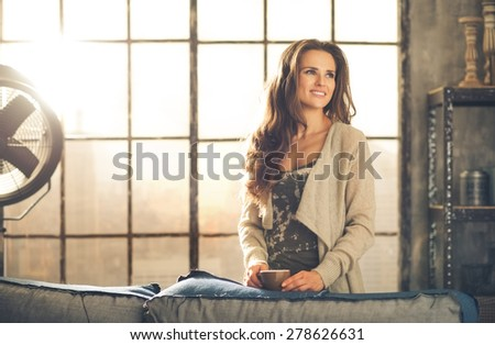 A brunette woman in comfortable clothing is smiling over her shoulder, resting a cup on the sofa. Looking up sideways and smiling, she is in a cozy atmosphere. Loft decoration details. Upper body. - stock photo