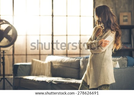 A brunette woman in comfortable clothing is standing in a loft living room, holding her phone, arms crossed, looking away. Urban chic loft decoration details and window. - stock photo