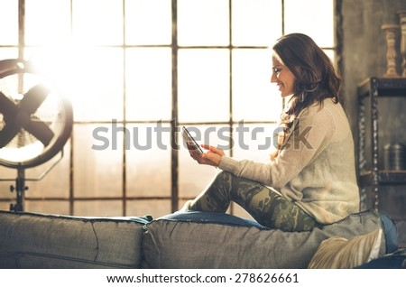 A brunette woman is smiling, looking down at her holding a tablet PC while sitting on the back of a sofa. Industrial chic ambiance and cozy atmosphere, sunlight is streaming through the loft window. - stock photo