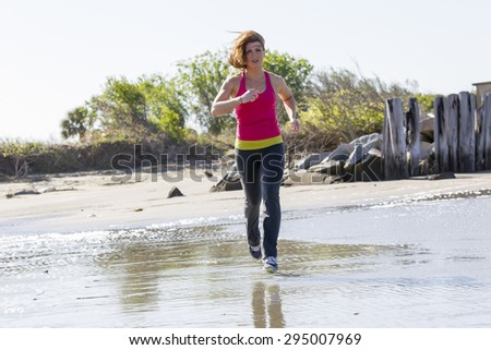 A brunette woman jogs along the beach on a sunny day - stock photo
