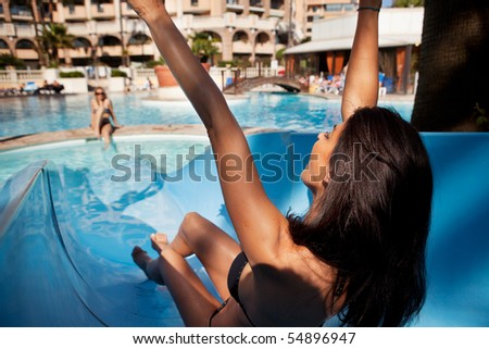 A brunette woman on an outdoor water slide at a hotel - stock photo