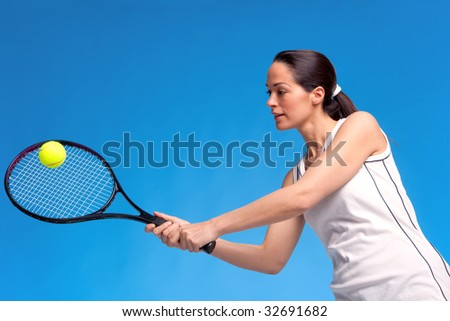 A brunette woman playing tennis against a blue background.