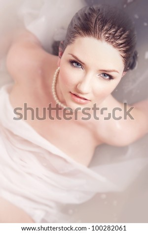 A brunette woman rising out of milky water - stock photo