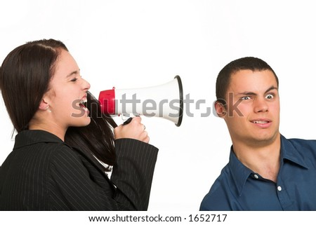 A brunette woman  yelling at her male business partner over a microphone.