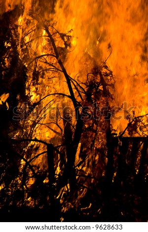 A brush fire next to a farm building - stock photo