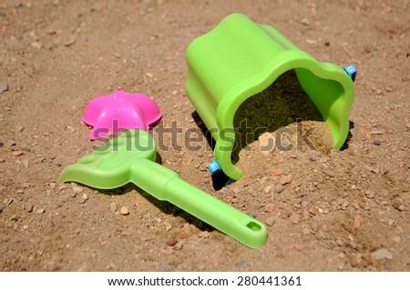 A bucket and a rake in a children's sandbox - stock photo