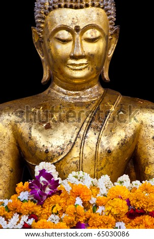 a buddhist statue with garland isolated on black background, Thailand - stock photo