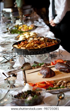 a buffet table with hot potatoes and a server in the background - stock photo