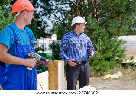 A builder and engineer standing paused in their work watching something on site looking off to the right side of the frame - stock photo