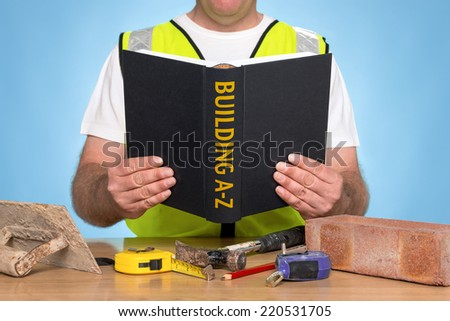 A builder sat at a desk reading a BUILDING A-Z book