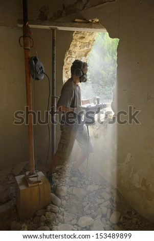 a builder that creates a door in an old stone wall - stock photo