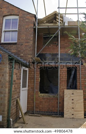 a building extension on the side of an edwardian character property - stock photo