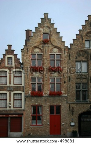 a building in Brugges Belgium with flowers in the windows.