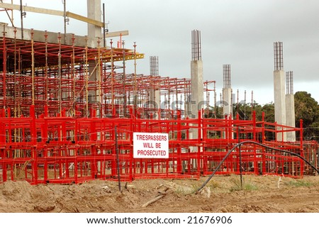 A building site with a big red and grey big scaffolding with yellow warning sign TRESPASSERS WILL BE PROSECUTED outdoors