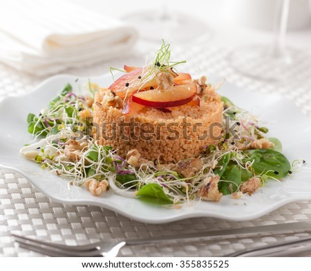 A bulgur salad with sprouts, spinach, nuts and plums.