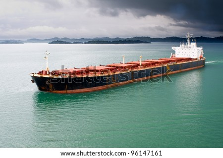 A bulk freighter travels through the Panama Canal under stormy skies - stock photo