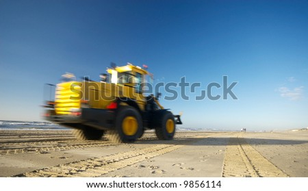 a bulldozer moving fast on the beach ( motion blur) - stock photo