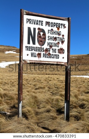 "A bullet-ridden sign on a farm in rural South Africa warns trespassers. The sign says: ""Private Property. No Fishing, Shooting, Hiking. Trespassers off the road will be prosecuted."""