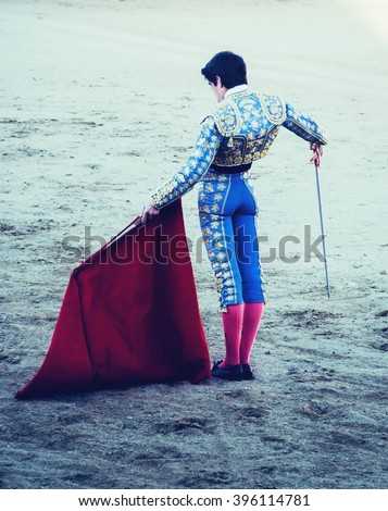A bullfighter awaiting for the bull in the bullring with estoque and muleta. Matador. Vignette effect - stock photo