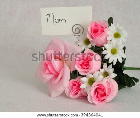A bunch of artificial flowers with a card with only the word mom isolated on a white background