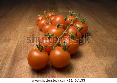 a bunch of baby tomatoes on a wooden table - stock photo