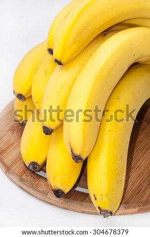 A bunch of beautiful bananas on a wooden kitchen board.