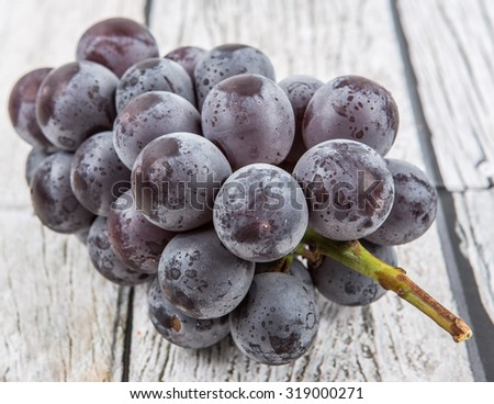 A bunch of black grapes over wooden background